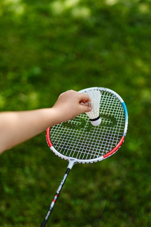 Person Holding White and Red Tennis Racket