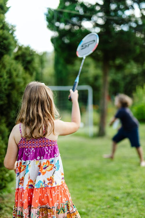 Girl in White Pink and Green Floral Tank Top Holding White and Black Tennis Racket