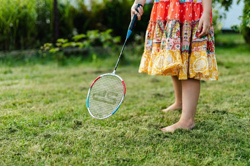 Woman in Red and White Floral Dress Holding Blue and White Tennis Racket