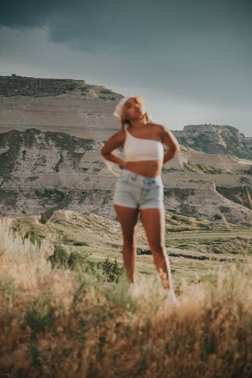 Blurred cool ethnic female in casual clothes standing on meadow against rocky mountains in sunny day