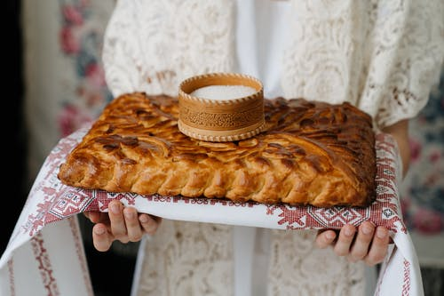 Person Holding Brown Pastry on White Plate
