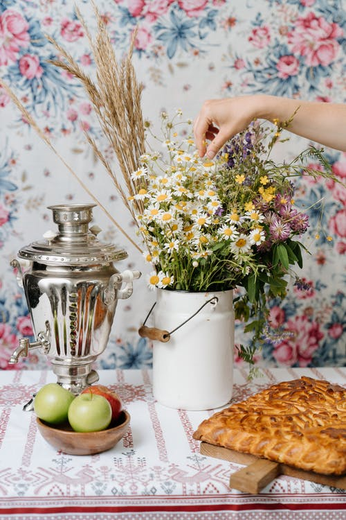 Person Holding White and Yellow Flowers in Vase