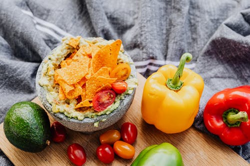 Orange and Green Bell Pepper on Brown Wooden Bowl