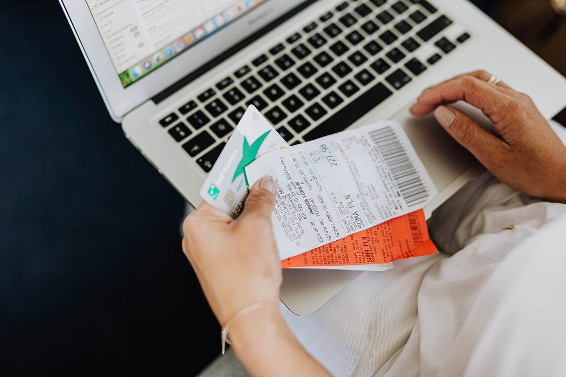 Person Using a Computer and Holding a Credit Card and Receipts