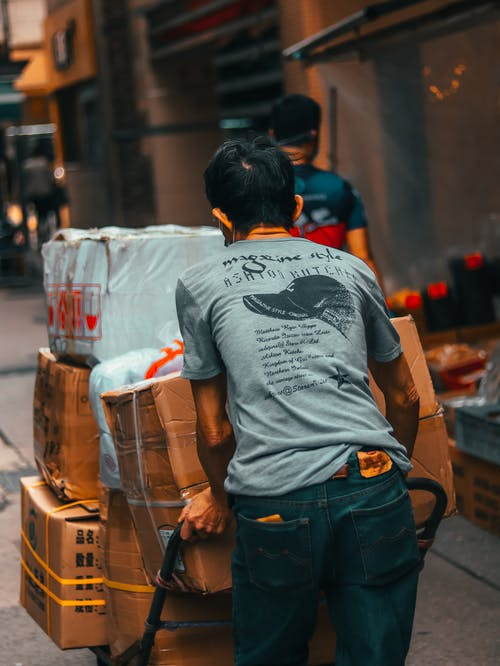 Unrecognizable male worker carrying cart with heavy carton boxes