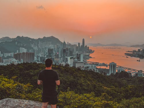 Anonymous male hiker enjoying sunset over modern coastal city from viewpoint