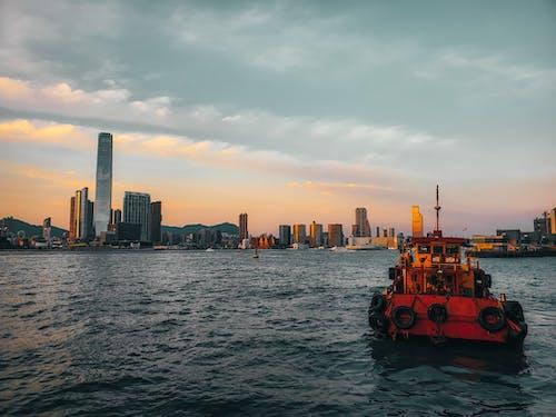 Boat sailing in sea near contemporary coastal city at sundown