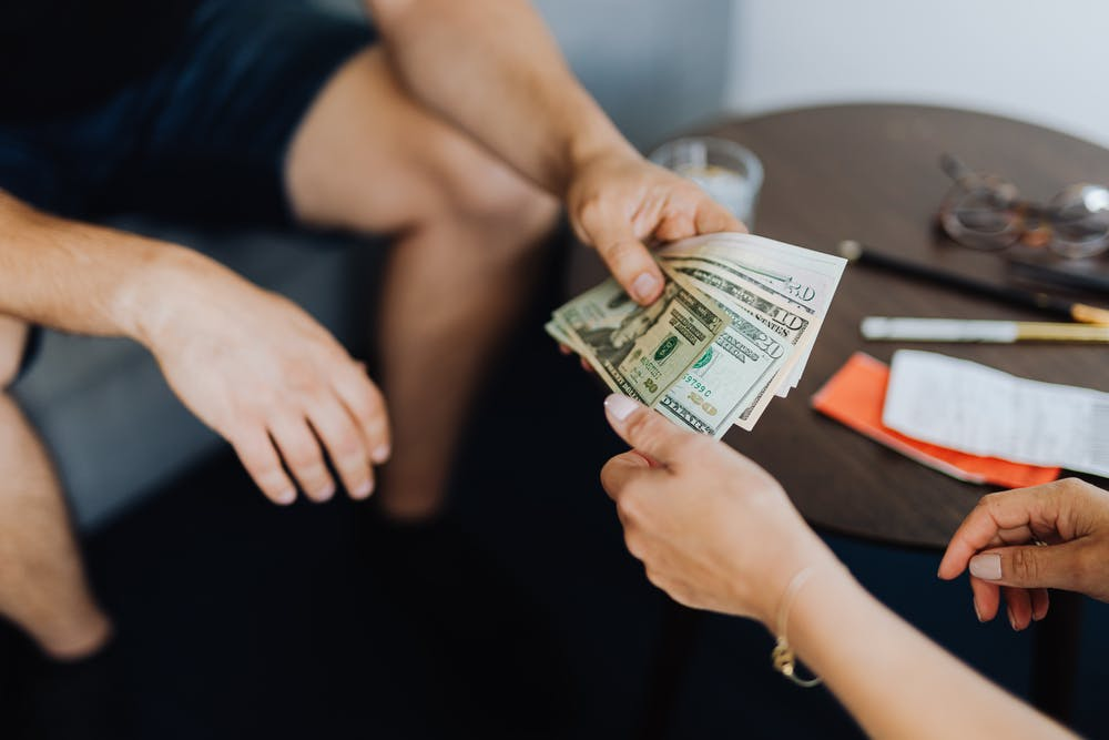 A person giving money to another person. | Photo: Pexels