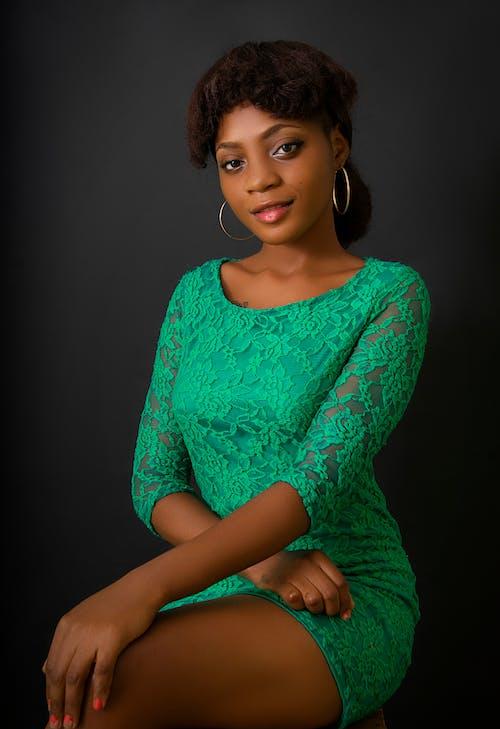 Elegant black woman in green dress in studio