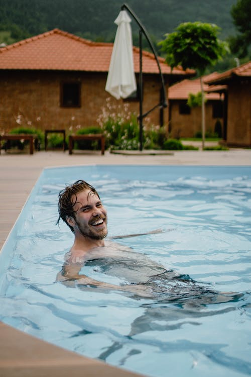 Happy man with long hair and beard swimming in pool near cottages against green hill
