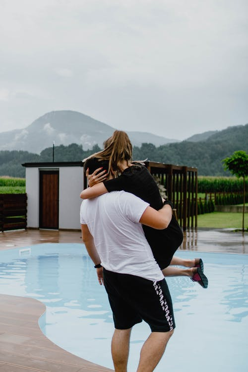 Man carruing woman in arms near swimming pool