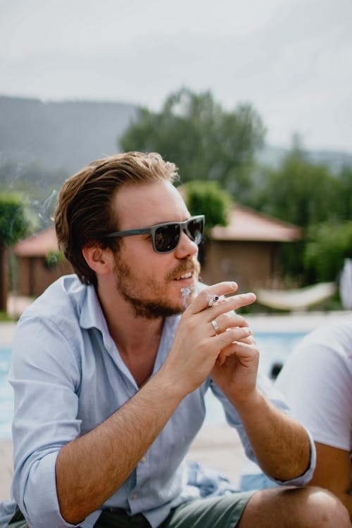 Cheerful man with hairstyle and beard in sunglasses and shirt sitting on resort and smoking cigarette against green trees