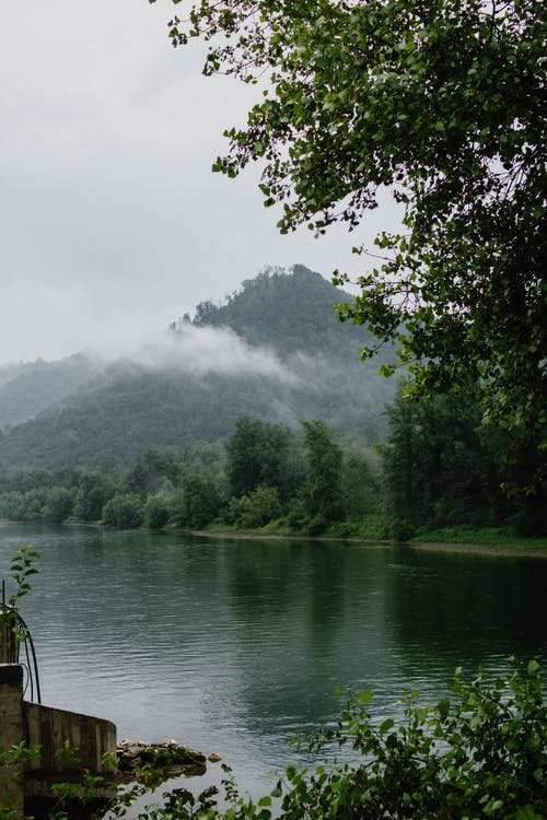 Picturesque scenery of calm water of lake surrounded by green trees and mountains in cloudy day