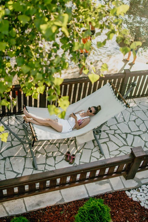 Woman lying on hammock under tree in sunny day