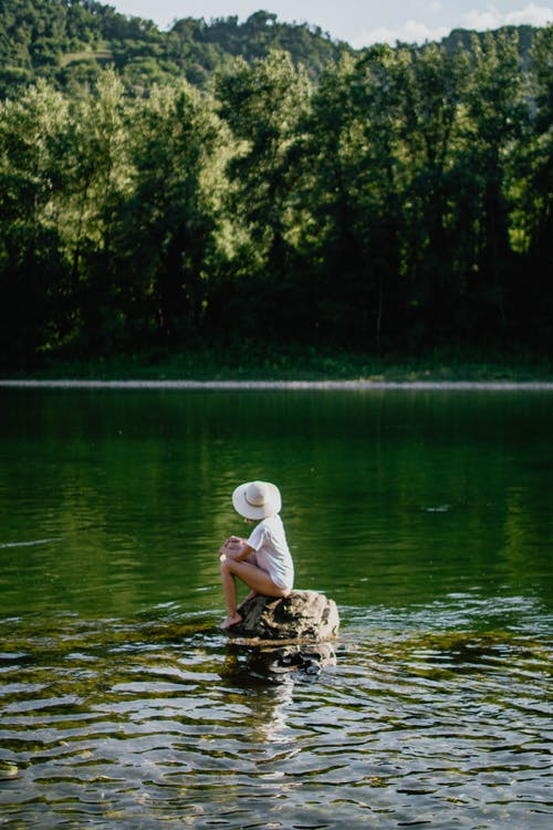 Unrecognizable female in hat sitting on rock in calm water and looking on green forest