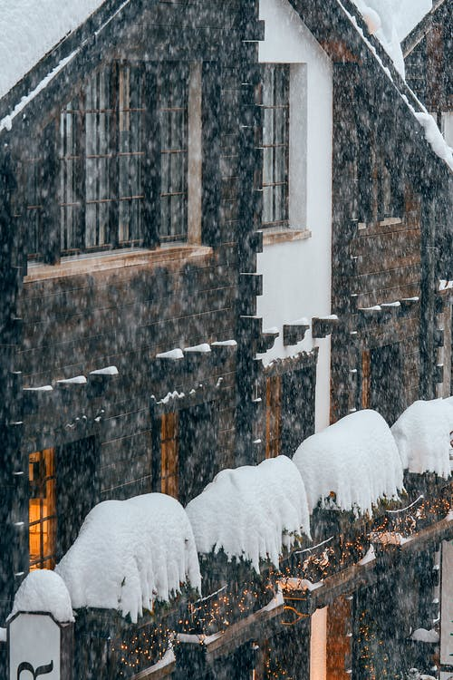 Facade of contemporary apartment building covered with thick layer of snow during intense snowstorm on freezing winter day