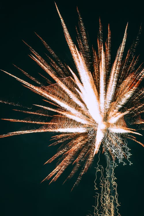 Glowing bright fireworks in dark sky