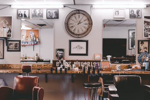 Stylish cozy interior design of modern hairdressing studio or barbershop with leather chairs stylish souvenirs and framed photos on walls