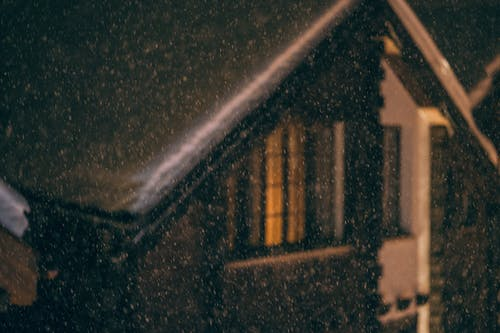 Exterior of small wooden cottage with snow on roof and burning electric lights in window during snowfall at cold winter night