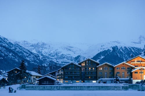 Residential cottages surrounded by snowy mountains in countryside