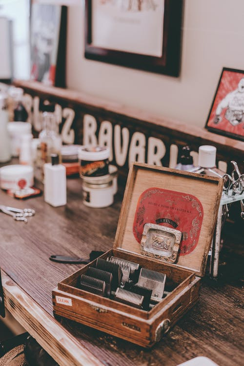 From above of various attachments for electric shaver placed in vintage wooden box in traditional barbershop