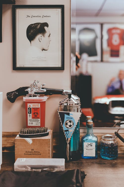 Various hair care products and comb placed near mirror on wooden table of old fashioned barbershop