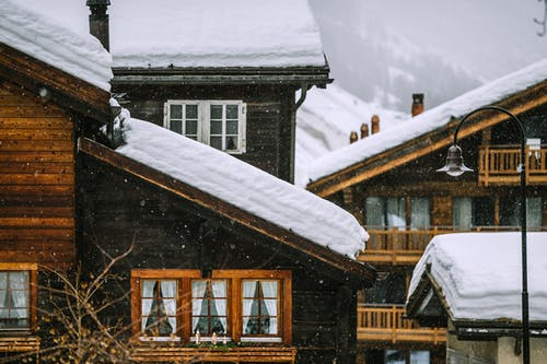 Wooden houses covered with snow in mountainous valley in winter