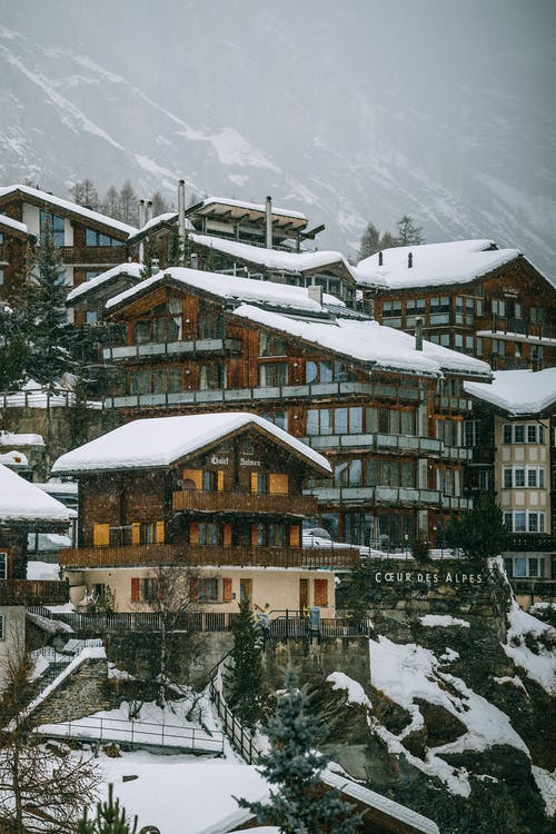 Alpine village with residential houses and buildings surrounded by massive snowy mountains on foggy day