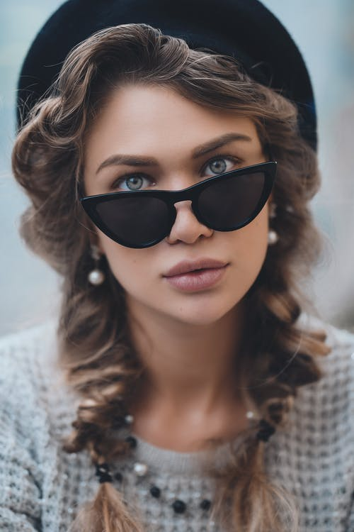 Stylish woman in sunglasses looking at camera