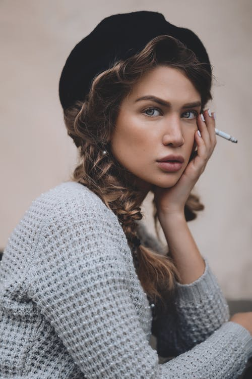 Woman in beret with cigarette touching face