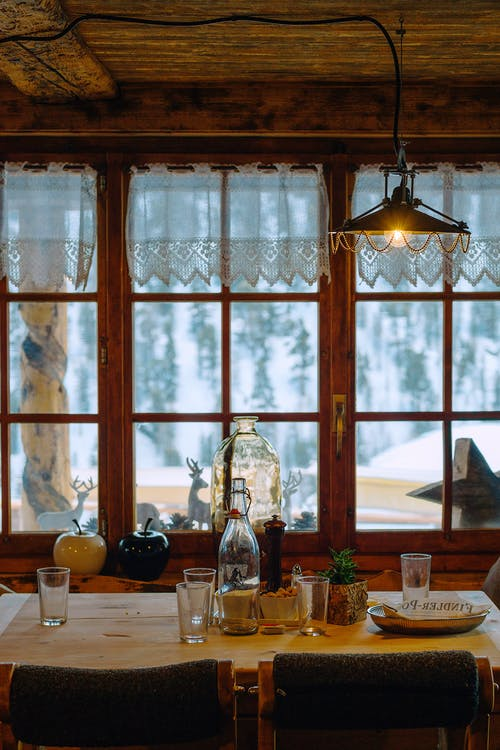 Interior of old wooden building with decor on table and windowsill against snowy trees in countryside