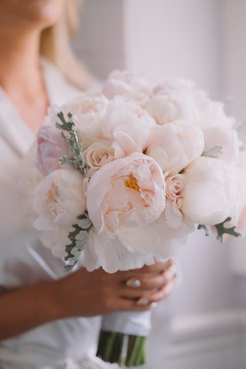 Crop anonymous woman holding blossoming bridal bouquet with pleasant aroma during festive event in house