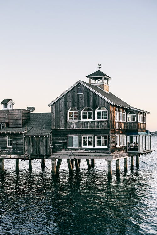 Old house on pier in ocean at sunset