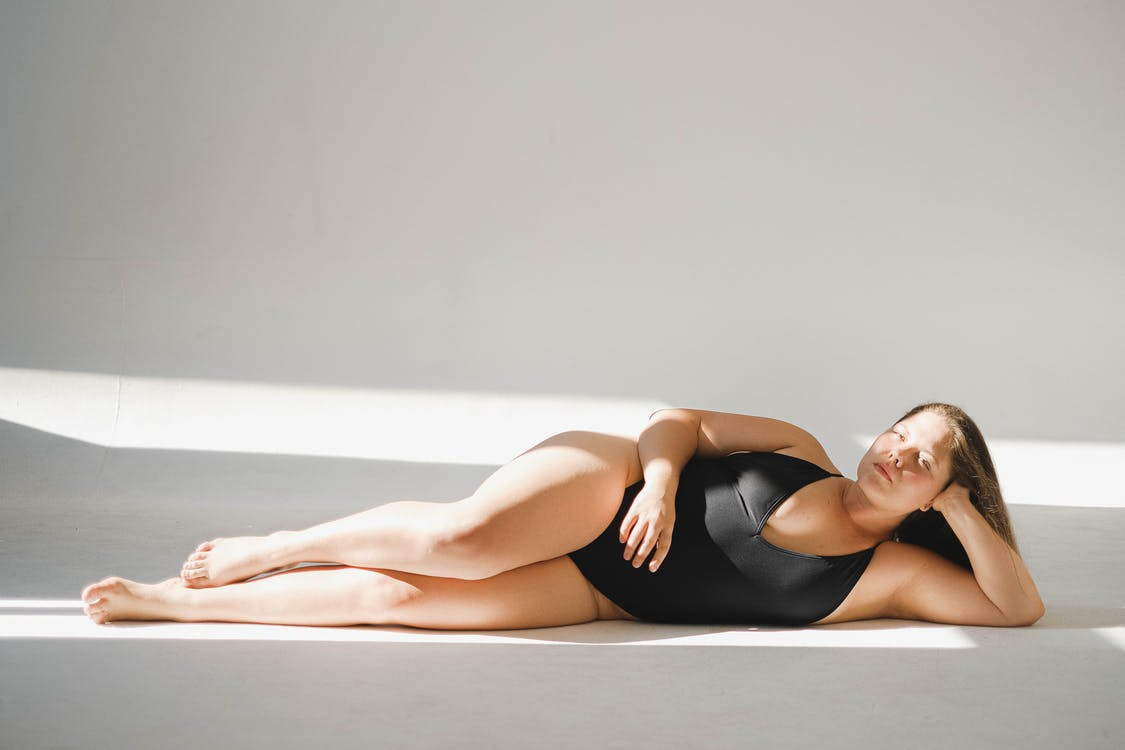 Woman in Black Tank Top Lying on Floor