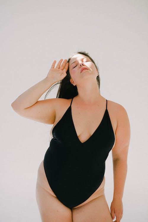 Woman in a Black Bikini Posing with Her Eyes Closed