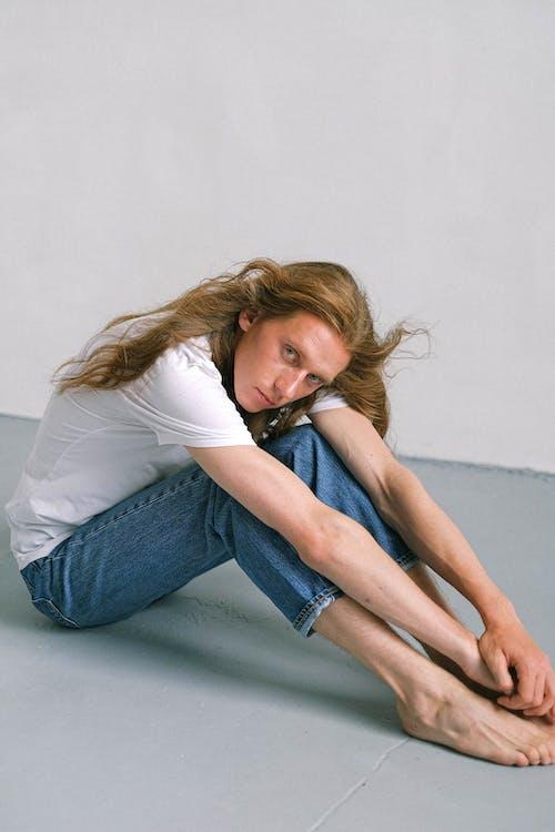 Serene androgynous man sitting on floor