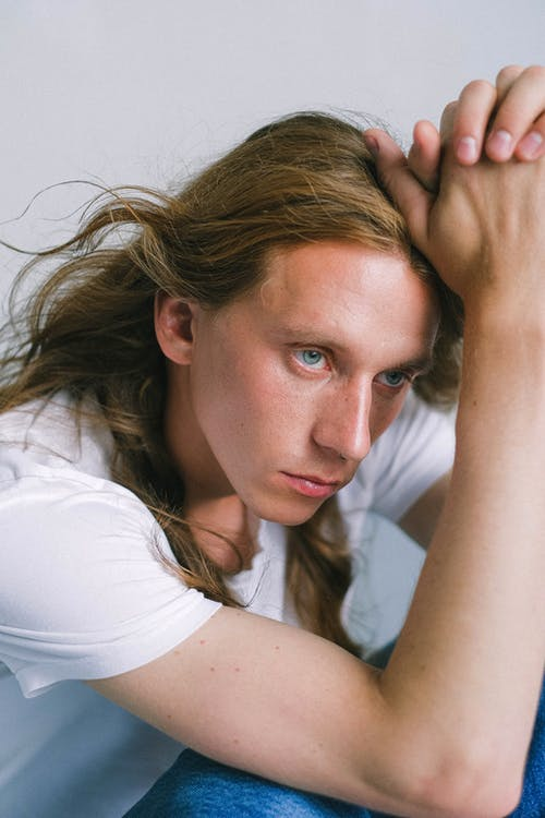 Wistful androgynous man touching head and sitting in light studio