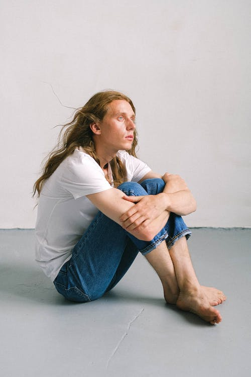 Wistful androgynous man embracing knees in light studio