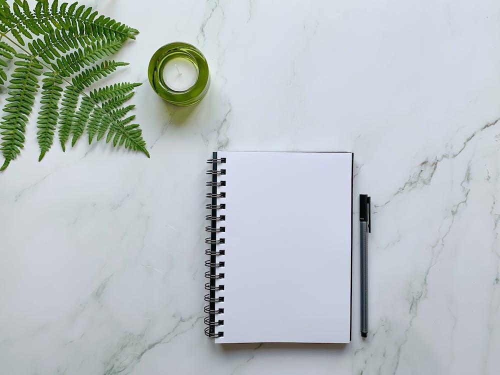 White Spiral Notebook Beside Green Ceramic Mug