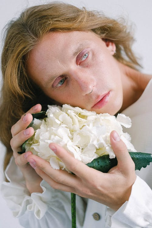 Dreamy young male model holding bunch of hydrangeas in hands
