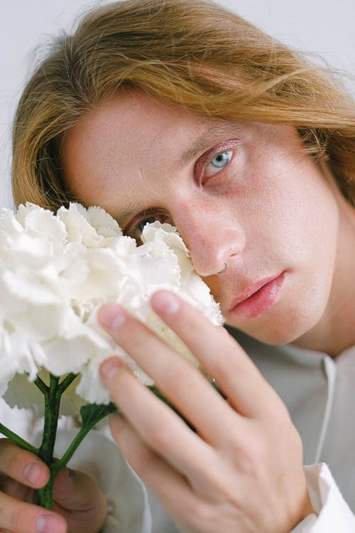 Pensive young androgynous male covering eye with flowers