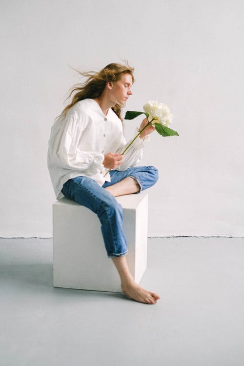 Calm young woman relaxing on stool with hortensia in hand