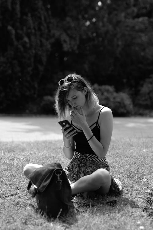 Woman in Tank Top and Skirt Sitting on Grass Field