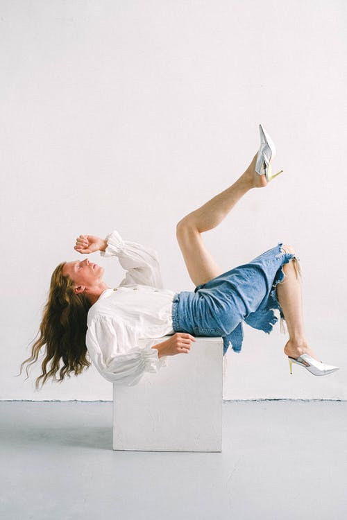 Side view of eccentric gender fluid young guy with long wavy hair in denim skirt and white blouse lying on cube with raised legs