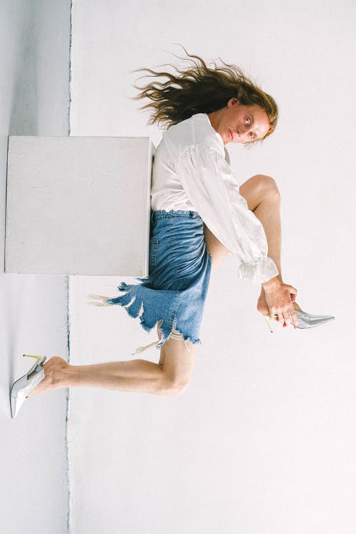 Serious young gender fluid man wearing shoes while lying on white cube