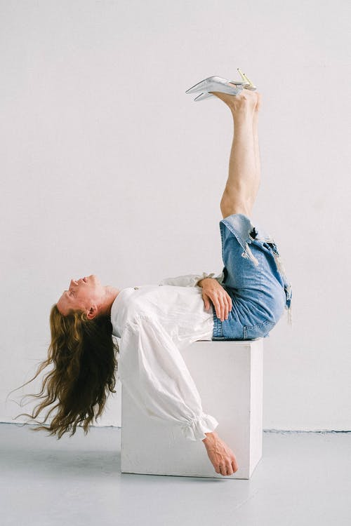 Side view of young eccentric androgynous man with long wavy hair in feminine outfit lying on cube with raised legs in white studio