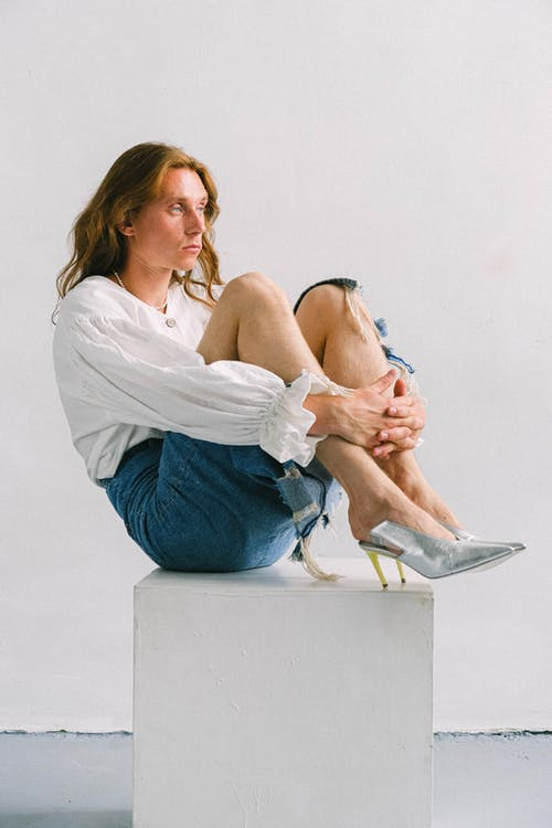 Serious androgynous man embracing knees on cube in studio