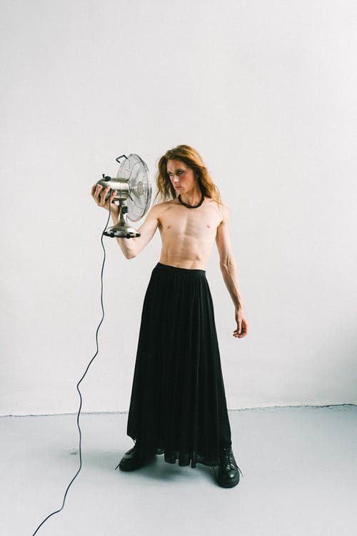 Full body of unemotional young shirtless male in black skirt with reddish hair looking at ventilator while standing next to white wall in bright room