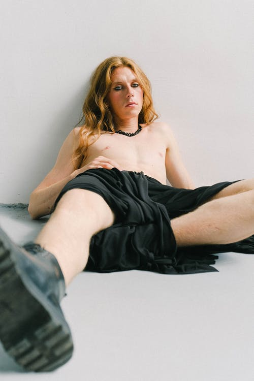 Full body of emotionless young slender shirtless male in black skirt and boots leaning to white wall while lounging in bright studio in daytime