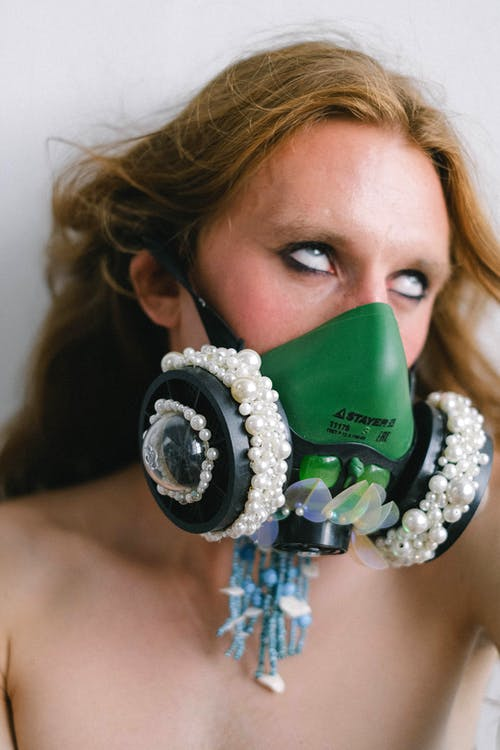 Anonymous eccentric shirtless androgynous man with long hair in stylish respirator covered with pearls rolling eyes against white background